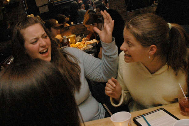 Times Union staff photo Michael P. Farrell--Trivia team mates (center) Kerry Levis (left) and Sara Welch (right) discuss a trivia answer during a Tueday trivia night at Bombers on Lark Street in Albany, New York Tuesday March 1, 2005.