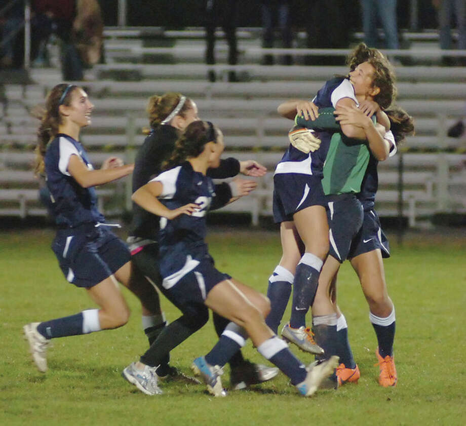 Hour photo/John NashWilton goalkeeper Liz Forster, right, embraces teammate Lindsay Knutson as other Warriors rush to celebrate the Warriors 4-2 advantage in penalty kicks, giving them a 2-1 win over Farmington in Monday's second round of the CIAC Class L state tournament.