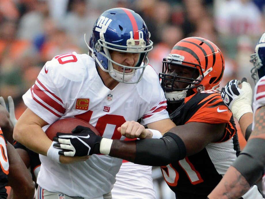 New York Giants quarterback Eli Manning (10) is sacked by Cincinnati Bengals defensive end Robert Geathers (91) in the first half of an NFL football game on Sunday, Nov. 11, 2012, in Cincinnati. (AP Photo/Michael Keating) / FR170759 AP