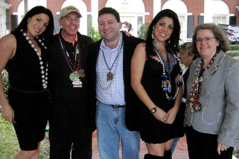 CORRECTS TO SAY KELLEY IS AN UNPAID SOCIAL LIASON TO MACDILL AFB, NOT STATE DEPARTMENT - In this Jan. 30, 2010 photo, Natalie Khawam, left, Gen. David Petraeus, Scott and Jill Kelley, and Holly Petraeus watch the Gasparilla parade from the comfort of a tent on the Kelley's front lawn in Tampa, Fla. Jill Kelley is identified as the woman who received threatening emails from Gen. David Petraeus' paramour, Paula Broadwell. Jill Kelley serves as an unpaid social liaison to MacDill Air Force Base in Tampa, where the military's Central Command and Special Operations Command are located. (AP Photo/The Tampa Bay Times, Amu Scherzer) TAMPA OUT; CITRUS COUNTY OUT; PORT CHARLOTTE OUT; BROOKSVILLE HERNANDO TODAY OUT; USA TODAY OUT; TV OUT; INTERNET OUT; MAGS OUT / Tampa Bay Times