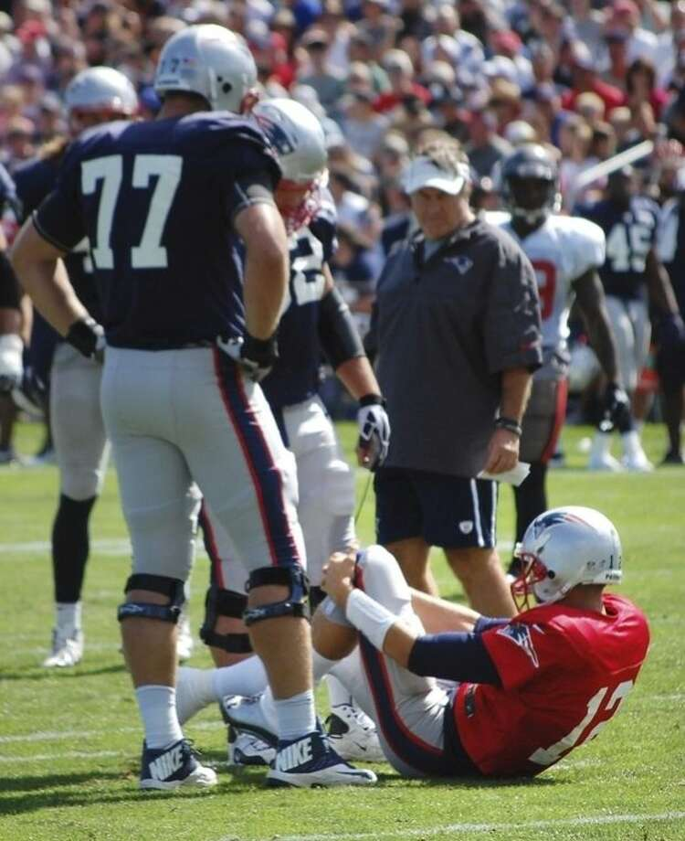 New England Patriots quarterback Tom Brady grabs his left knee after an apparent injury during a joint workout with the Tampa Bay Buccaneers at NFL football training camp, in Foxborough, Mass., Wednesday, Aug. 14, 2013. Watching Brady are Patriots tackle Nate Solder (77) and head coach Bill Belichick. (AP Photo/Will DiTullio)
