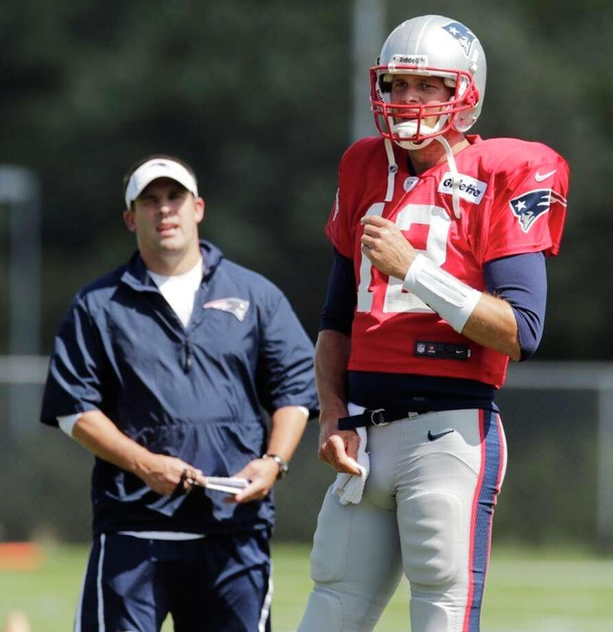 New England Patriots quarterback Tom Brady (12) talks with offensive coordinator Josh McDaniels during a joint workout with the Tampa Bay Buccaneers at NFL football training camp, in Foxborough, Mass., Wednesday, Aug. 14, 2013. (AP Photo/Charles Krupa) / AP