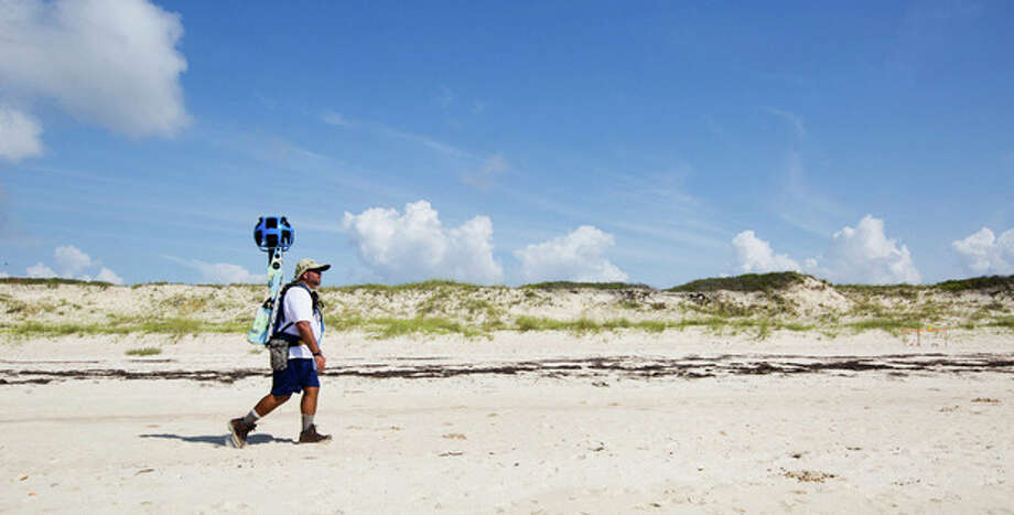 In this photo taken July 30, 2013, and made available by Visit Florida, Gregg Matthews carries a Google street view camera as he walks recording St. George Island sand dunes in the Florida Panhandle. Visit Florida, the state's tourism agency, partnered with Google in the effort to map all 825 miles of Florida's beaches. The Florida project is the first large-scale beach mapping project. (AP Photo/Visit Florida, Colin Hackley) / Visit Florida