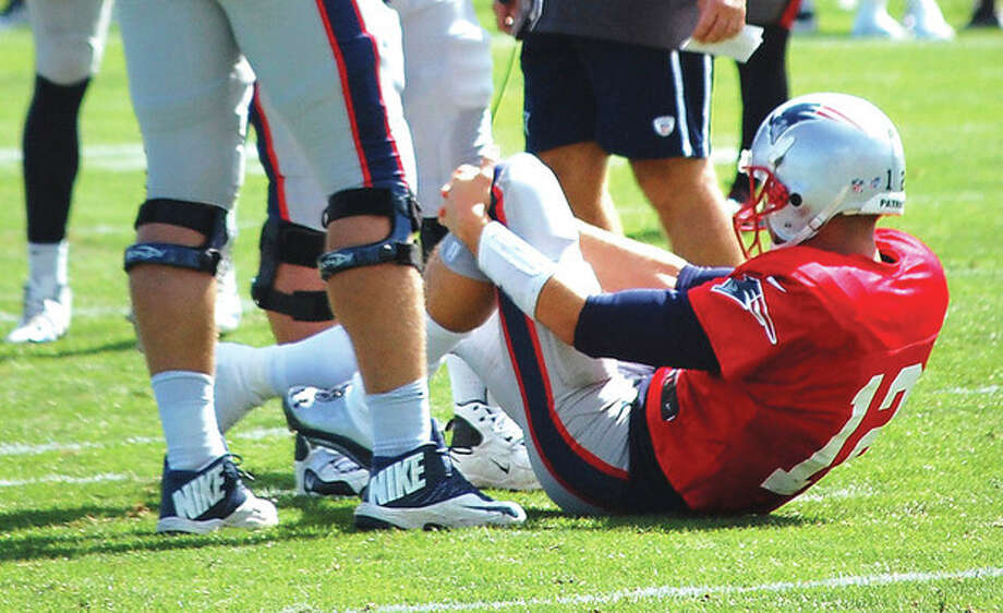 AP photoNew England Patriots quarterback Tom Brady grabs his left knee after going down during a joint workout with the Tampa Bay Buccaneers Wednesday in Foxborough, Mass. Sources say Brady suffered a knee sprain. / AP