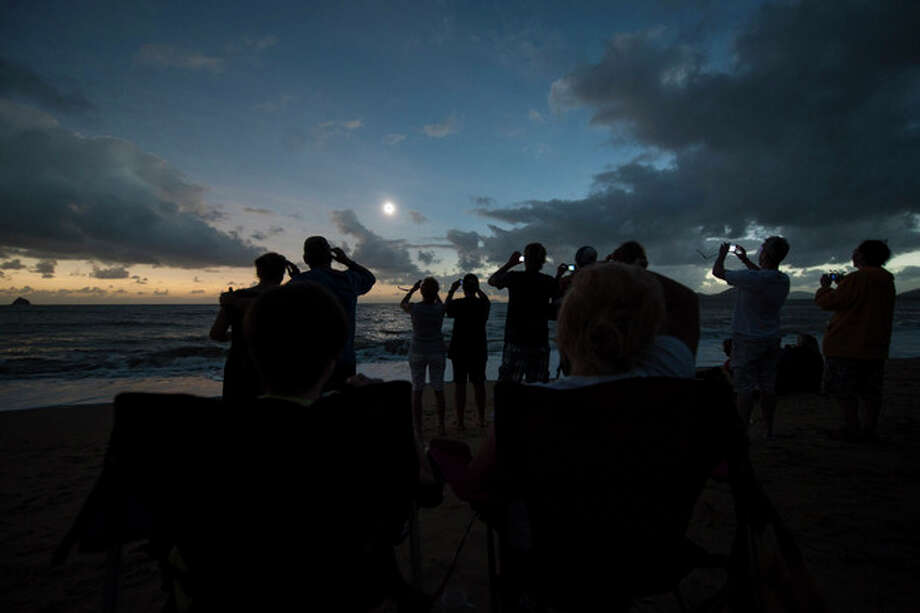 In this photo released by Tourism Queensland, people gather on Palm Cove beach in Queensland state, Australia, to watch a total solar eclipse Wednesday, Nov. 14, 2012. Starting just after dawn, the eclipse cast its 150-kilometer (95-mile) shadow in Australia's Northern Territory, crossed the northeast tip of the country and was swooping east across the South Pacific, where no islands are in its direct path. (AP Photo/Tourism Queensland, Murray Anderson-Clemence) EDITORIAL USE ONLY / Tourism Queensland