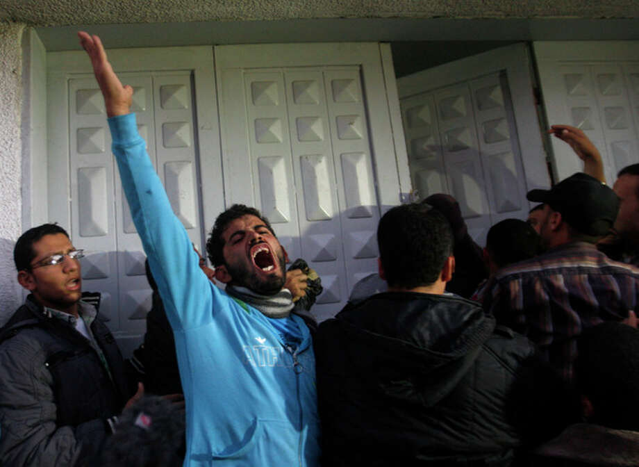 Palestinian men react at hospital after the body of Ahmed Jabari, head of the Hamas military wing, was brought, in Gaza City, Wednesday, Nov. 14, 2012. The Israeli military said its assassination of the Hamas military commander marks the beginning of an operation against Gaza militants. (AP Photo/Hatem Moussa) / AP
