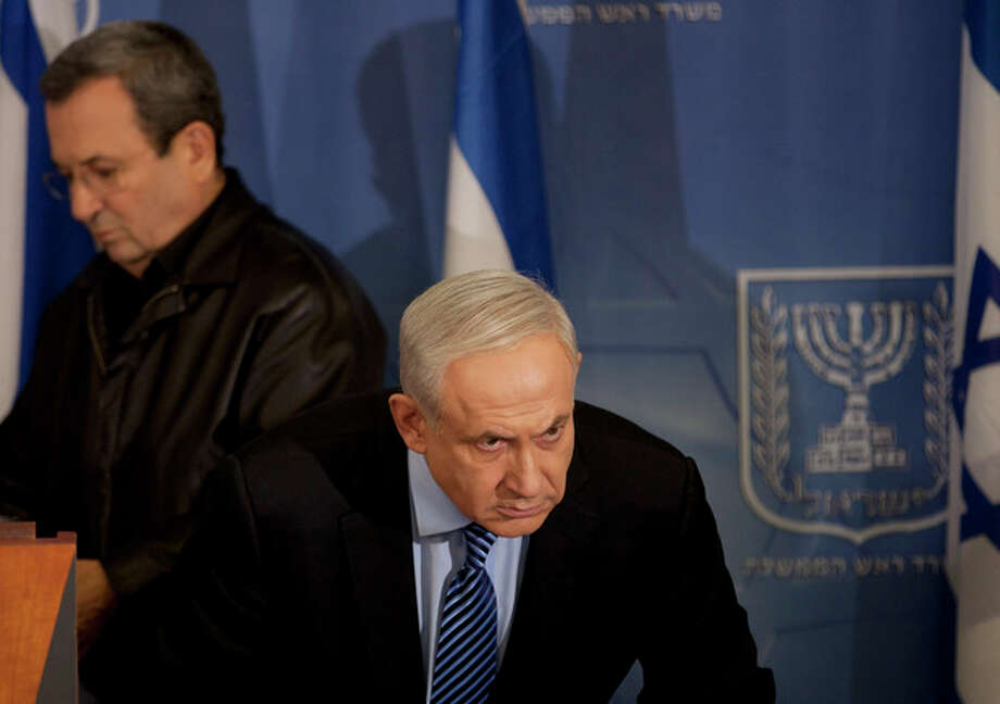 """Israel's Prime Minister Benjamin Netanyahu looks on as Israel's Defense Minister Ehud Barak, left, goes to deliver a statement to the media at Hakirya a military base in Tel Aviv, Israel, Wednesday, Nov. 14, 2012. Israel's prime minister says the military is prepared to broaden its operation against Hamas targets in Gaza. Benjamin Netanyahu says Israel cannot tolerate continued rocket attacks against its citizens. In his first comments since Israel killed the commander of the Hamas military wing, Netanyahu said Wednesday that Israel is """"prepared to expand the operation"""". (AP Photo/Ariel Schalit) / AP"""