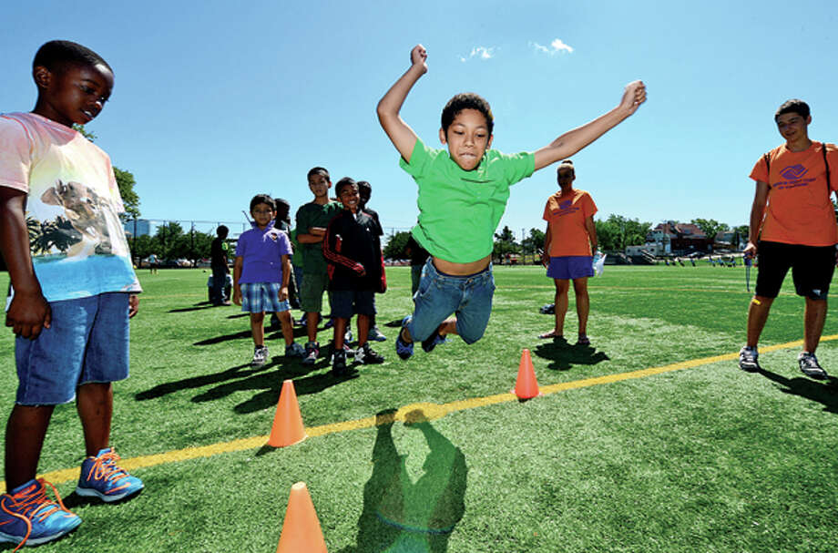 Gustavo Letona, 9, competes in the long jump as The Boys & Girls Club of Stamford hosts their First Annual Community Fitness Day Wednesday. Approximately 250 children will participated in a variety of fun fitness events to reinforce the importance of living an active, healthy lifestyle. Hour photo / Erik Trautmann / (C)2013, The Hour Newspapers, all rights reserved