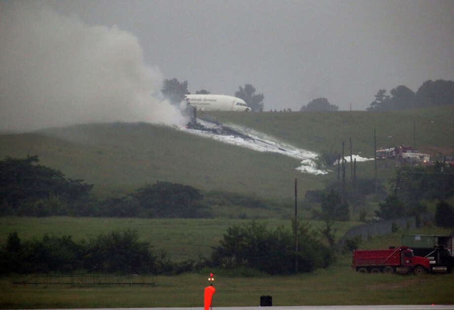 A UPS cargo plane lies on a hill at Birmingham-Shuttlesworth International Airport after crashing on approach, Wednesday, Aug. 14, 2013, in Birmingham, Ala. Toni Herrera-Bast, a spokeswoman for Birmingham's airport authority, says there are no homes in the immediate area of the crash. (AP Photo/Hal Yeager) / FR56789 AP