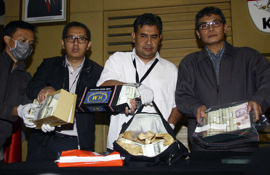 Officials of Indonesia's Corruption Eradication Commission (KPK) show banknotes confiscated from the Chairman of the Special Task Force for Upstream Oil and Gas Business Rudi Rubiandini who was arrested for allegedly receiving bribes from a private oil company, during a press conference in Jakarta, Indonesia, Wednesday, Aug. 14, 2013. (AP Photo) / AP