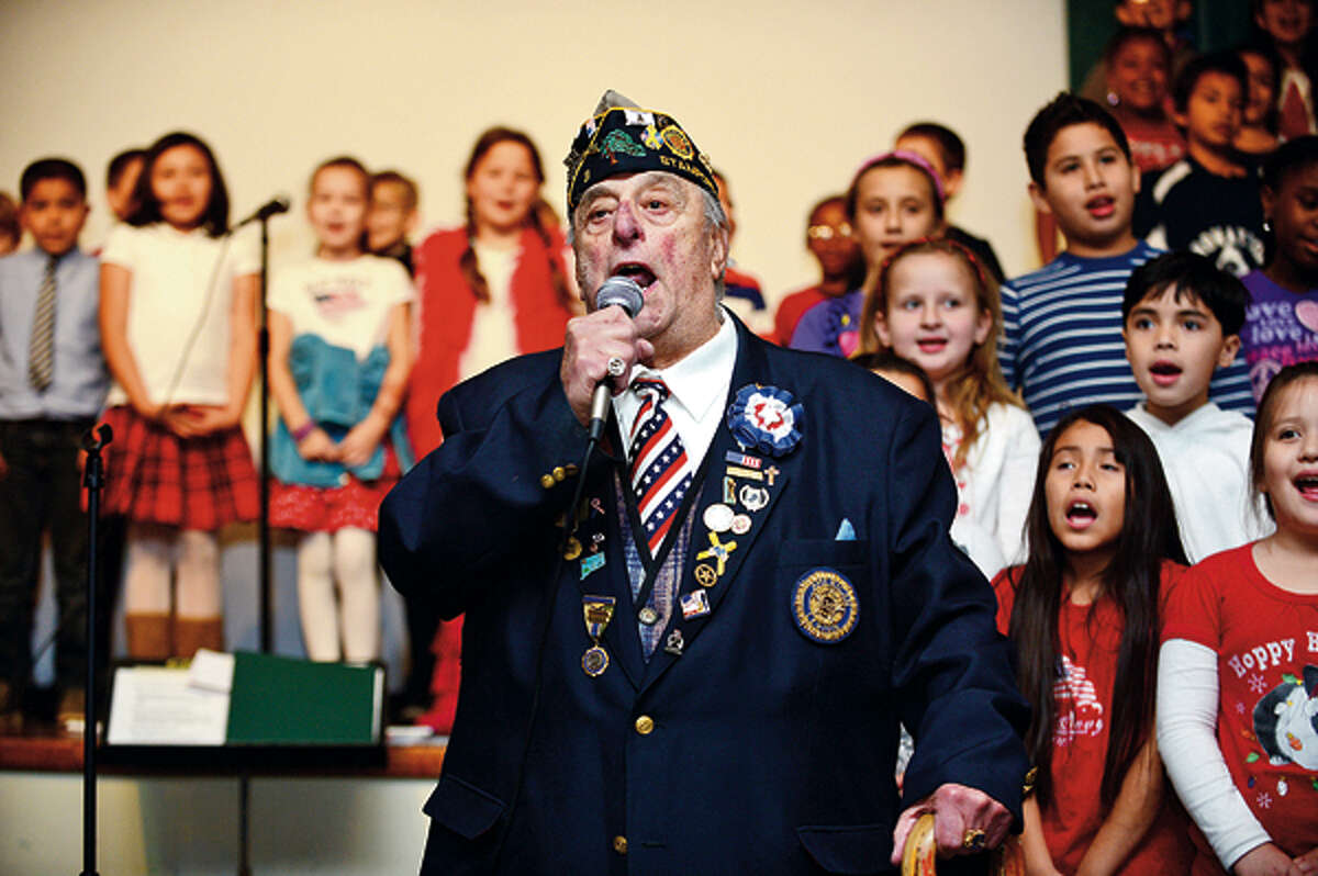Veteran Carmine Vaccaro sings God Bless America as Springdale School 3rd graders put on a patriotic performance to thank area veterans for their service Wednesday. Hour photo / Erik Trautmann