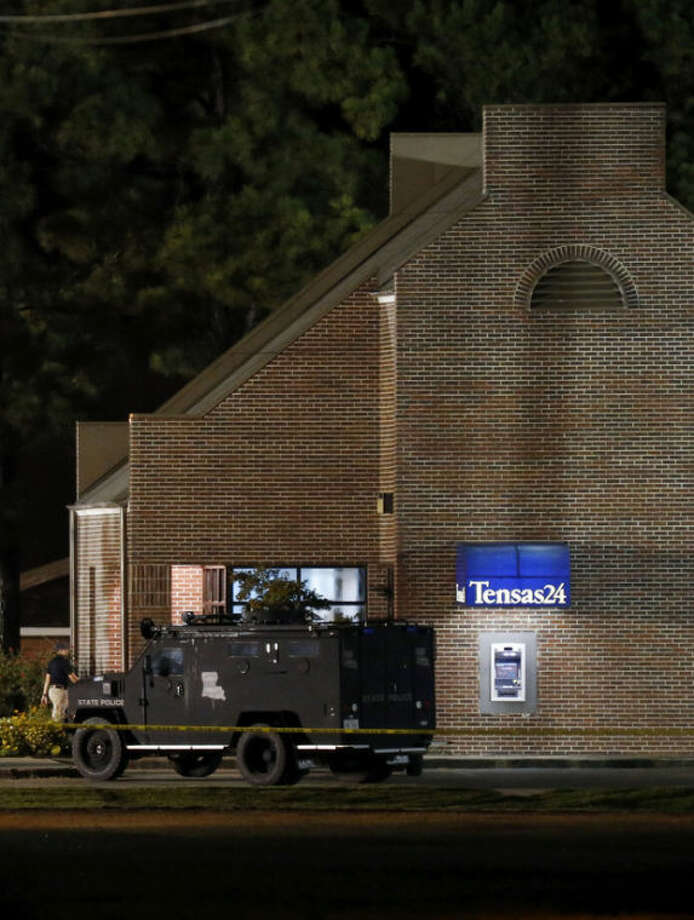 A SWAT vehicle sits outside the Tensas State Bank in St. Joseph, La., as investigators work throughout the early morning hours Wednesday, Aug. 14, 2013, in the bank where a gunman took three people hostage Tuesday. The suspect, identified as 20-year-old Fuaed Abdo Ahmed later released one hostage but around midnight shot the two remaining hostages, killing one of them before being shot and killed by police authorities said. (AP Photo/Rogelio V. Solis)