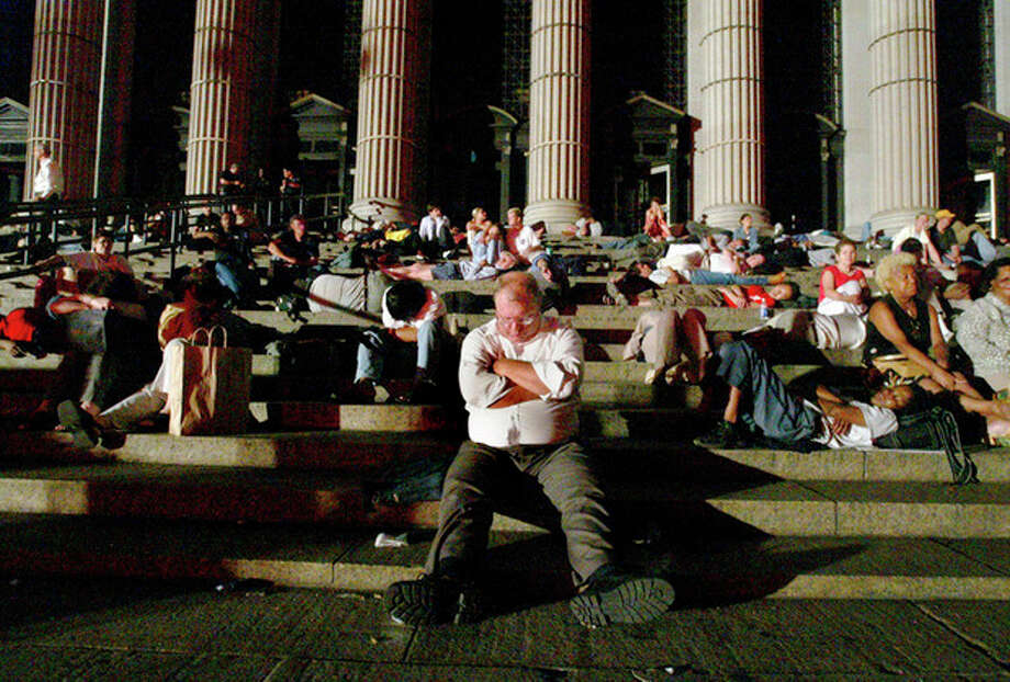 FILE- In this Aug. 15, 20113 file photo, commuters sleep on the steps of the Central Post Office in New York after being stranded following a massive electrical blackout. About 50 million people lost power Aug. 14, 2003, when a tree branch touching high-power transmission lines in Ohio started an outage that cascaded across a broad swath from Michigan to New England and Quebec. (AP Photo/ Mike Appleton, File) / AP
