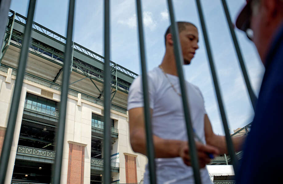 The upper-level platform from where 30-year-old Ronald Homer fell into the player's parking lot at Monday night's game is seen at top left as Atlanta Braves' Andrelton Simmons signs autographs for fans while arriving at Turner Field, Tuesday, Aug. 13, 2013, in Atlanta. Homer's death appeared to be an accident, authorities said. At least four witnesses told police that no one else was standing near him when he fell over a fourth-level railing into the parking lot for players. It was at least the third time a sports fan has fallen from a stadium in Atlanta in the past year. (AP Photo/David Goldman) / AP