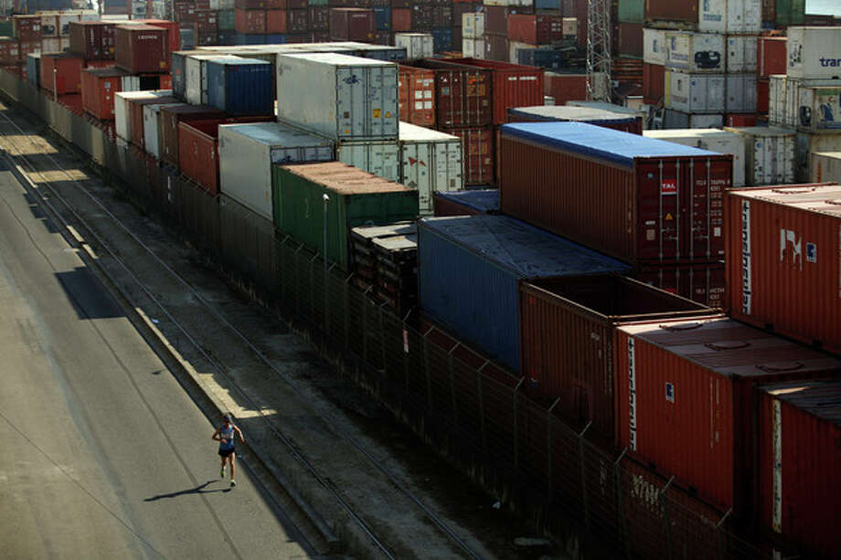 A man runs past containers placed at Lisbon's Santa Apolonia port, Wednesday, Aug. 14, 2013. Eurostat, the European Union's statistics office, said the 17 EU countries that use the euro saw their collective economic output increase by 0.3 percent in the April to June period from the previous quarter. That's the first quarterly growth since the eurozone slipped into recession in the last three months of 2011. (AP Photo/Francisco Seco) / AP