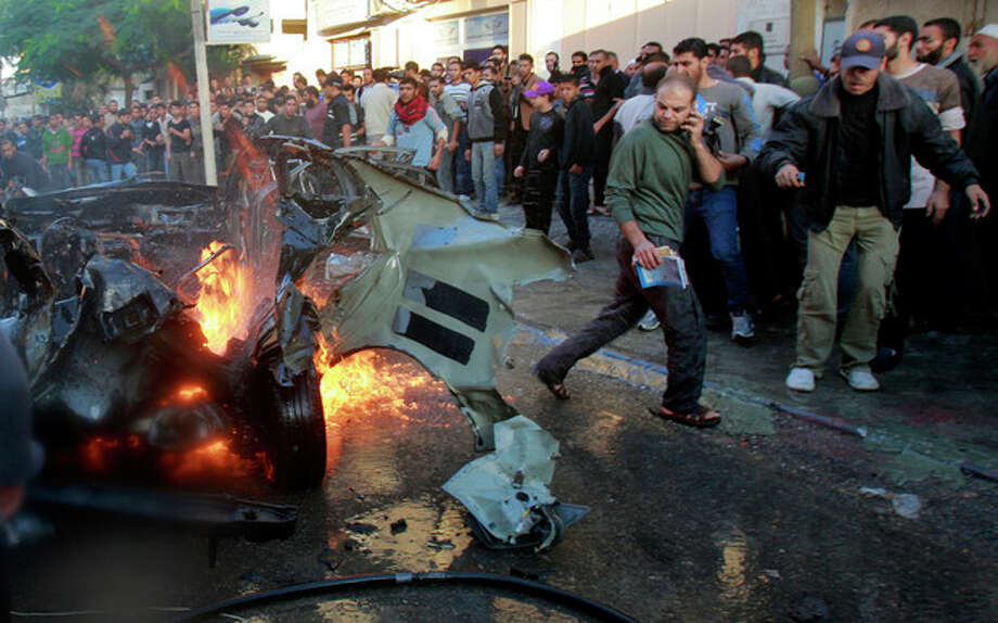 People look at a wreckage of the car in which was killed Ahmed Jabari, head of the Hamas military wing in Gaza City, Wednesday, Nov. 14, 2012. The Israeli military said its assassination of the Hamas military commander marks the beginning of an operation against Gaza militants. (AP Photo/Adel Hana) / AP