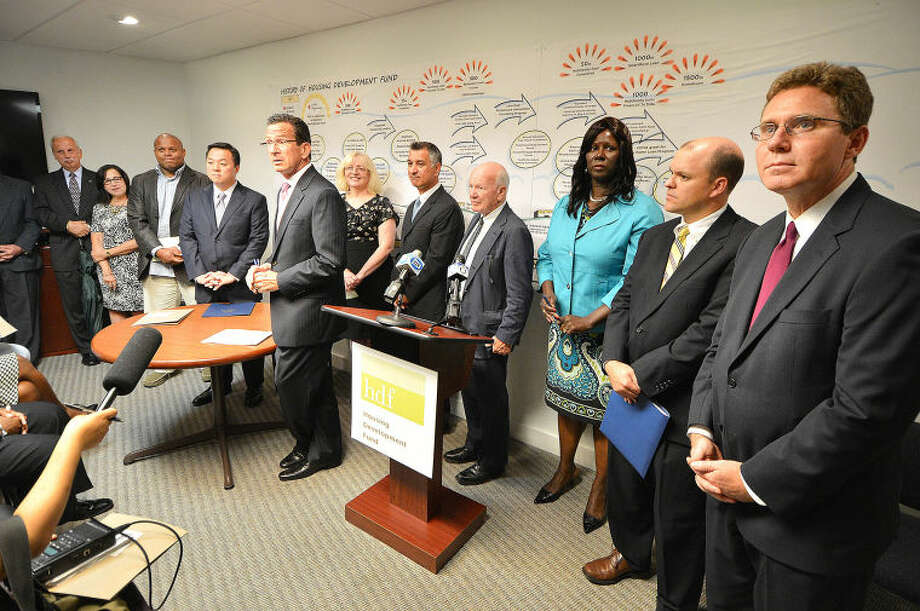Gov. Dannel P. Malloy talks with guests after signing a homeowners protection bill at the offices of the Housing Development Fund in Stamford.