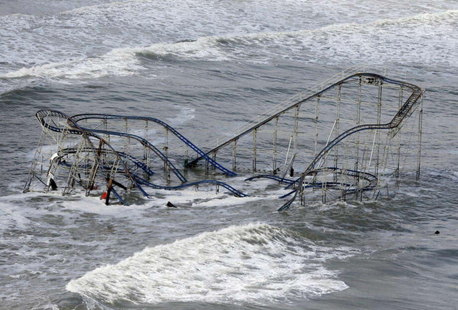 FILE - In this Wednesday, Oct. 31, 2012 file photo, waves wash over a roller coaster from a Seaside Heights, N.J. amusement park that fell in the Atlantic Ocean during Superstorm Sandy. Superstorm Sandy, the rare and devastating Northeast storm, and an election that gave Democrats gains have put global warming back in the picture. (AP Photo/Mike Groll) / AP