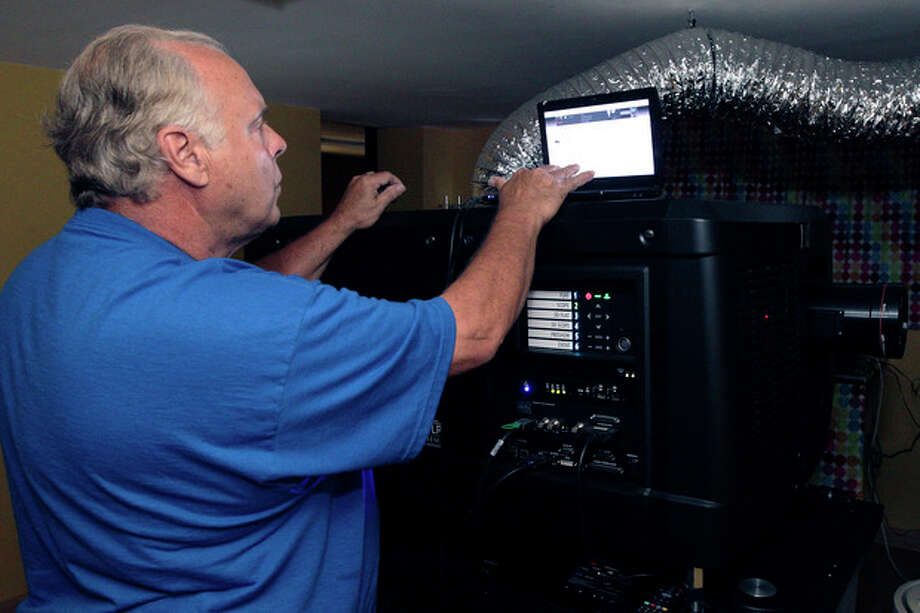 In this July 20, 2013 photo, Walt Effinger, owner of the Skyview drive-in theater, starts a movie on his new digital projector in Lancaster, Ohio. The Skyview was the first drive-in theater in Ohio to convert to a digital projector. The latest threat to the existence of drive-in theaters is the conversion from 35mm film to digital prints and the expense involved in converting projectors to the new format. (AP Photo/Jay LaPrete) / FR52593 AP