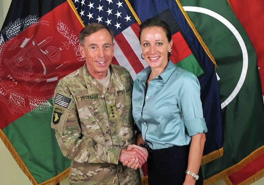 """FILE - This July 13, 2011, photo made available on the International Security Assistance Force's Flickr website shows the former Commander of International Security Assistance Force and U.S. Forces-Afghanistan Gen. Davis Petraeus, left, shaking hands with Paula Broadwell, co-author of his biography """"All In: The Education of General David Petraeus."""" The affair between retired Army Gen. David Patraeus and author Paula Broadwell is but an extreme example of the love/hate history between biographers and their subjects. (AP Photo/ISAF, file) / ISAF"""