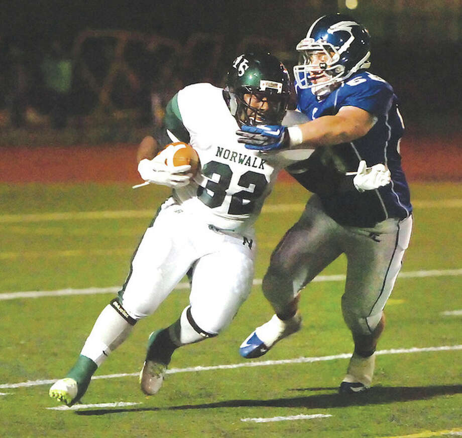 Hour Photo/Alex von KleydorffNorwalk's Tomar Joseph, left, tries to fend off the tackle of Fairfield Ludlowe's Jake Garrell during Thursday night's FCIAC football game at Taft Field. Ludlowe won the game, 21-20 in overtime. / 2012 The Hour Newspapers