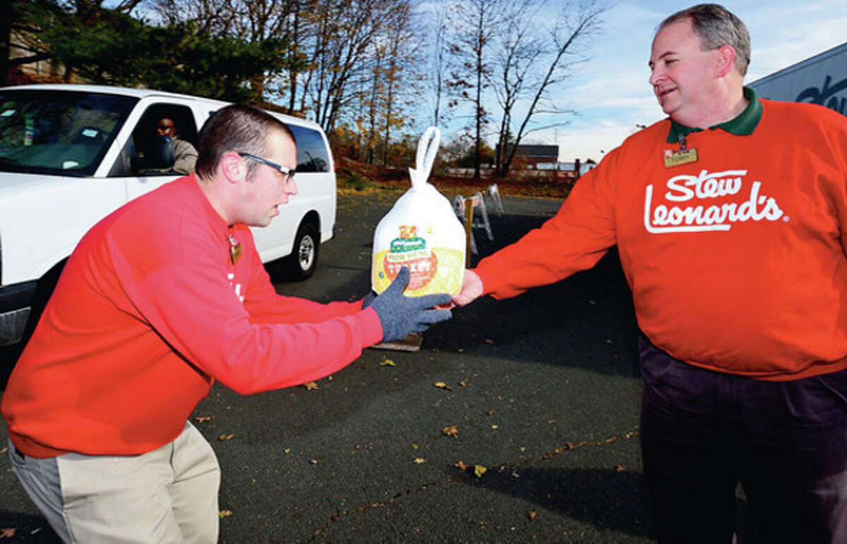 """Perry Landsman and Terry Scott help as Stew Leonard's 33rd Annual """"Turkey Brigade"""" distributes 1,929 turkeys Thursday to more than 100 churches, civic groups, elderly housing and senior nutrition programs, and schools the Norwalk and other communities that Stew Leonard'ss serve to help provide Thanksgiving day meals for families in need. Hour photo / Erik Trautmann"""