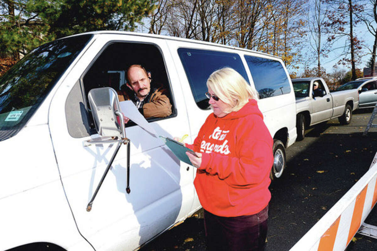 """Peter Loskocinski of Cornerstone CHristian Center gets checked in by Patty Guthman as the Stew Leonard's 33rd Annual """"Turkey Brigade"""" distributes 1,929 turkeys Thursday to more than 100 churches, civic groups, elderly housing and senior nutrition programs, and schools the Norwalk and other communities that Stew Leonard'ss serve to help provide Thanksgiving day meals for families in need. Hour photo / Erik Trautmann"""