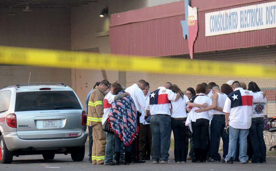 Parade participants and pubic safety officials huddle after a trailer carrying wounded veterans in a parade was struck by a train in Midland, Texas, Thursday, Nov. 15, 2012. Authorities say four people are dead and 17 others are injured after a Union Pacific train slammed into the parade float. (AP Photo/Reporter-Telegram, James Durbin) / Reporter-Telegram