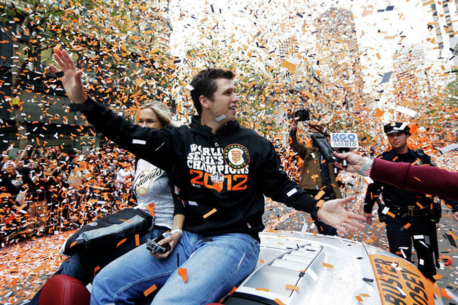 FILE - In this Oct. 31, 2012, file photo, San Francisco Giants catcher Buster Posey waves and is showered with confetti during their victory parade for winning baseball's World Series on Market Street in San Francisco. Posey is the favorite to win National League Most Valuable Player, to be announced Thursday, Nov. 15, 2012. (AP Photo/Marcio J. Sanchez, File) / AP