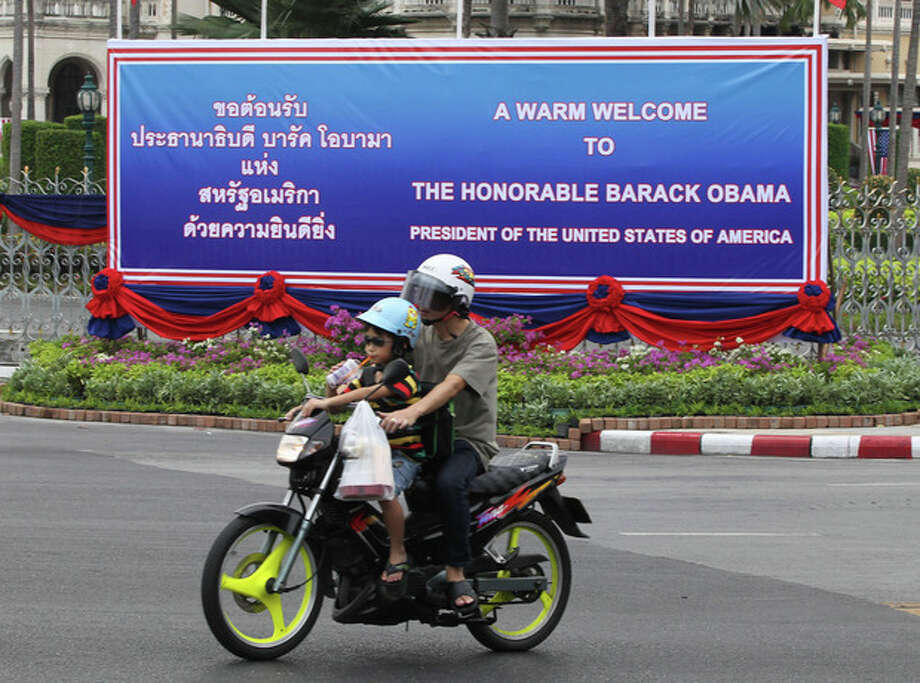 A man rides on a motorbike with a child past a welcoming banner for U.S. President Barack Obama erected outside the government house in Bangkok, Thailand Saturday, Nov. 17, 2012. Obama will arrive in Thailand on Sunday, Nov. 18, 2012 as part of his southeast Asian nations tour which includes Myanmar and Cambodia. (AP Photo/Apichart Weerawong) / AP