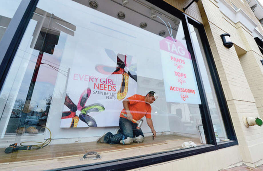 Hour photo / Erik TrautmannWorkers with Boston Premiere flooring install a new floor in the display window of The Loft in Westport on Friday. Many of the stores on and around Main Street in Westport were damaged by floodwaters during Hurricane Sandy and are now attempting to rebuild. / (C)2012, The Hour Newspapers, all rights reserved