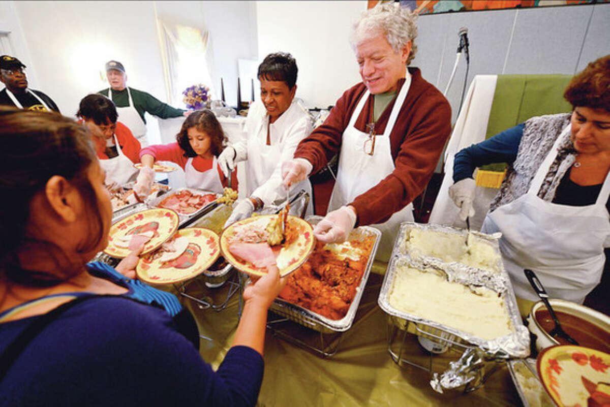 Barabara Thompson, Aniyah McCollum, Chris Burke, Jeff Mayer and Nancy Diamond volunteer at the annual Heart-to-Heart Foundation Thankgiving Feast Satuday at Calvary Baptist Church. Heart-to-Heart is a nonprofit formed by the Rev. Nellie Mann to help the needy. Hour photo / Erik Trautmann