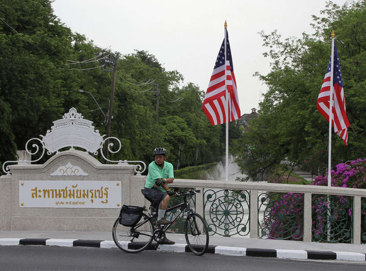 A cyclist waits for the traffic on a bridge decorated with US flags outside the government house in Bangkok, Thailand Saturday, Nov. 17, 2012. Obama will arrive in Thailand on Sunday, Nov. 18, 2012 as part of his southeast Asian nations tour which includes Myanmar and Cambodia. (AP Photo/Apichart Weerawong)