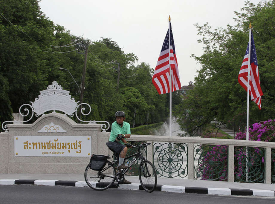 A cyclist waits for the traffic on a bridge decorated with US flags outside the government house in Bangkok, Thailand Saturday, Nov. 17, 2012. Obama will arrive in Thailand on Sunday, Nov. 18, 2012 as part of his southeast Asian nations tour which includes Myanmar and Cambodia. (AP Photo/Apichart Weerawong) / AP