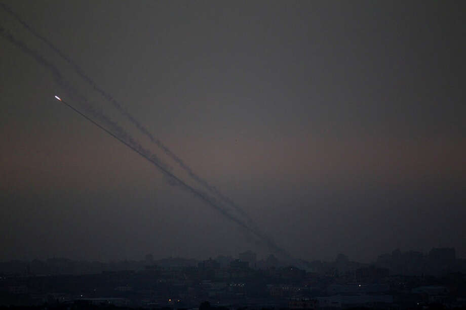 """Rockets lunched by Palestinian militants towards Israel make their way from the northern Gaza Strip, as seen from the Israel Gaza Border, southern Israel, Saturday, Nov. 17, 2012. The Israeli military says its """"Iron Dome"""" rocket-defence system has shot down an incoming projectile bound for Tel Aviv. (AP Photo/Ariel Schalit) / AP"""