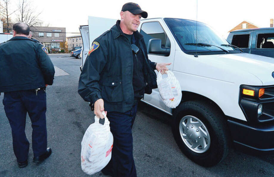Stamford Police officers including Erik Soderholm and the Stamford Police Association deliver 50 turkeys to the Food Bank of Lower Fairfield County Friday. Hour photo / Erik Trautmann / (C)2012, The Hour Newspapers, all rights reserved