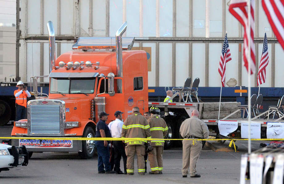 """Midland police, fire and sheriffs respond to an accident where a trailer carrying wounded veterans in a parade was struck by a train in Midland, Texas, Thursday, Nov. 15, 2012. """"Show of Support"""" president and founder Terry Johnson tells the Midland Reporter-Telegram that there are """"multiple, multiple"""" injuries and organizers still are trying to account for everyone. (AP Photo/Reporter-Telegram, James Durbin) / Reporter-Telegram"""
