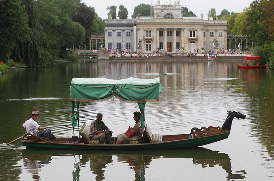This Aug. 6, 2013 photo shows visitors taking a boat ride on a pond in front of the Palace on the Isle in the Lazienki Park in Warsaw, Poland. Part of the Royal Route, the 17th century Royal Baths park is one of the most picturesque parks in Europe. There is a charge for visitors to the ornate Palace on the Isle, but you can just stroll for free in the surrounding park and gardens, around the pond. (AP Photo/Czarek Sokolowski) / AP