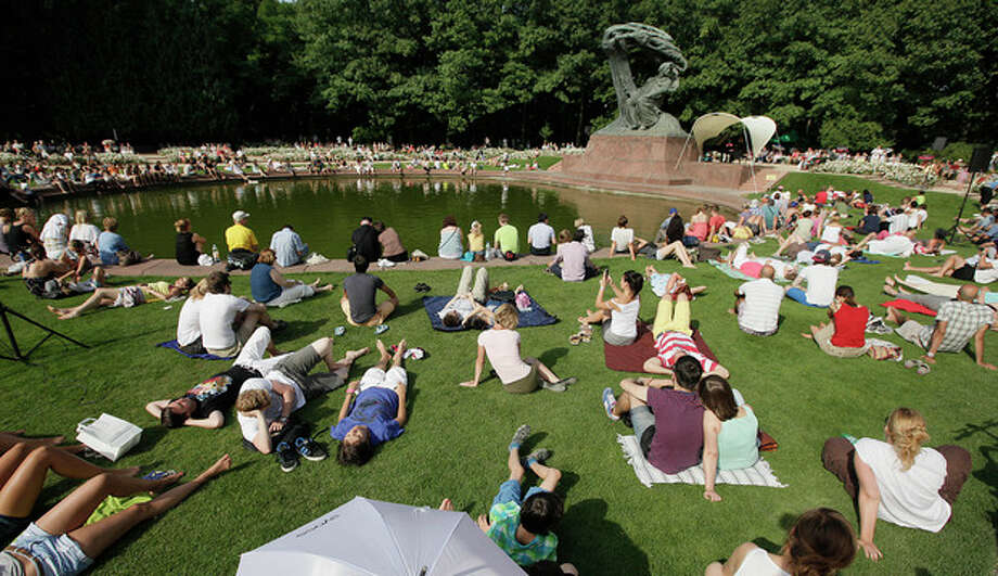 This Aug. 6, 2013 photo shows people gathered for a Chopin piano concert next to the composer's monument in the Lazienki Park in Warsaw, Poland. Free piano concerts of Frederic Chopin music are held by the Polish composer's monument on Sundays, May through September. Open air performances are to resume in the ancient-style Amphitheater in 2014. (AP Photo/Czarek Sokolowski) / AP