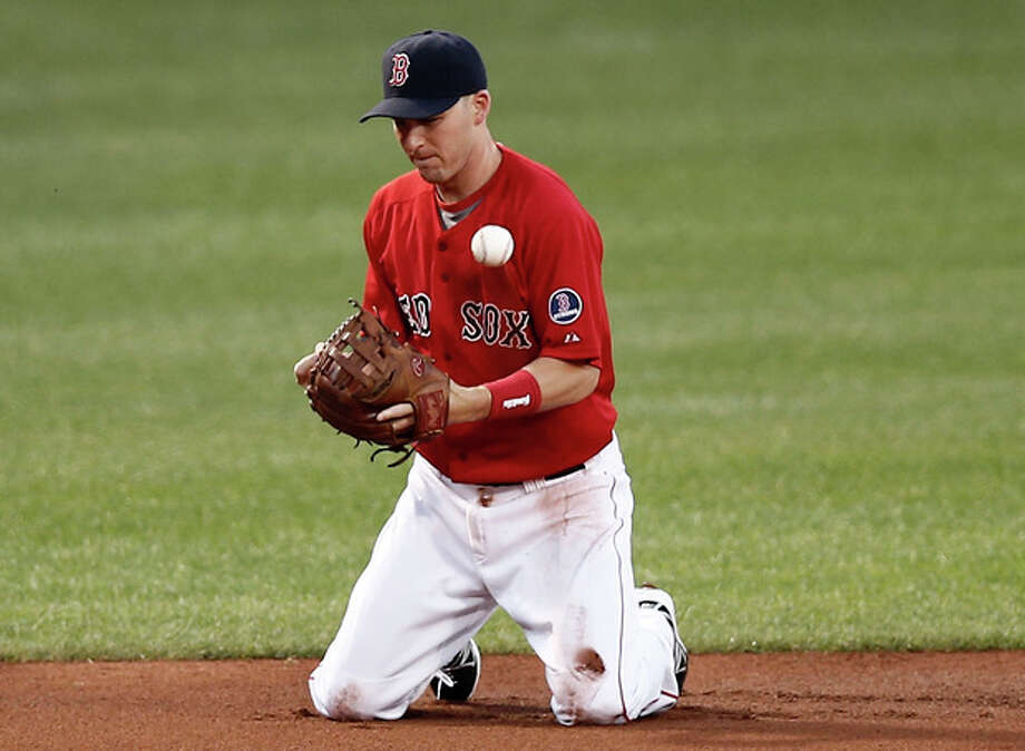 Boston Red Sox shortstop Stephen Drew bobbles a ball hit by New York Yankees' Alfonso Soriano, who reached first on the error during the first inning of a baseball game at Fenway Park in Boston on Friday, Aug. 16, 2013. (AP Photo/Winslow Townson) / FR170221 AP