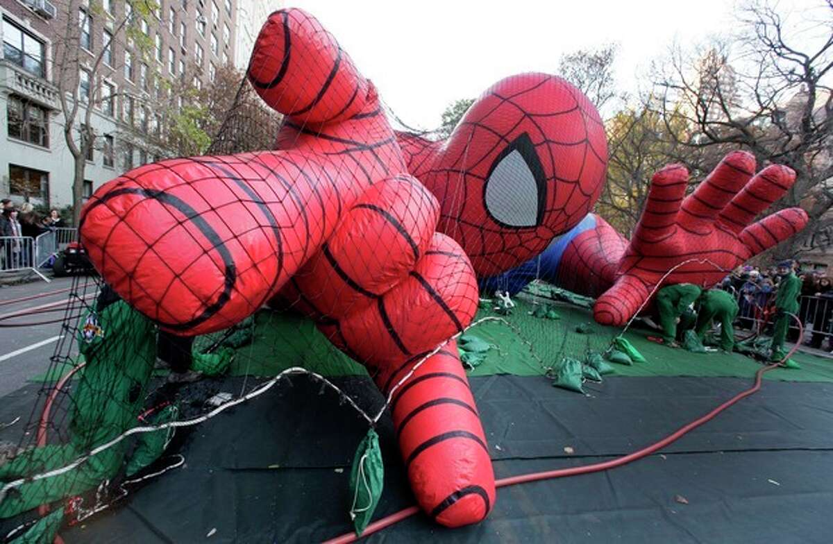Workers inflate the Spider-Man balloon for the 86th annual Macy's Thanksgiving Day Parade, on New York's Upper West Side, Wednesday, Nov. 21, 2012. More than 3 million people typically attend the event and it has a TV audience of 50 million. (AP Photo/Richard Drew)