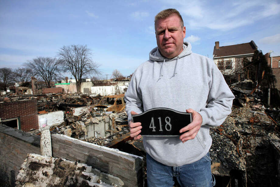 In this Sunday, Nov. 18, 2012 photo, Ray Marten poses with the street number sign recovered from the ashes of his fire-destroyed home in the Belle Harbor section of the Queens borough of New York. Marten is thankful that his teenage children are alive. The three of them narrowly escaped a fire that swept through their community the night Superstorm Sandy slammed into the East Coast. (AP Photo/Mark Lennihan) / AP