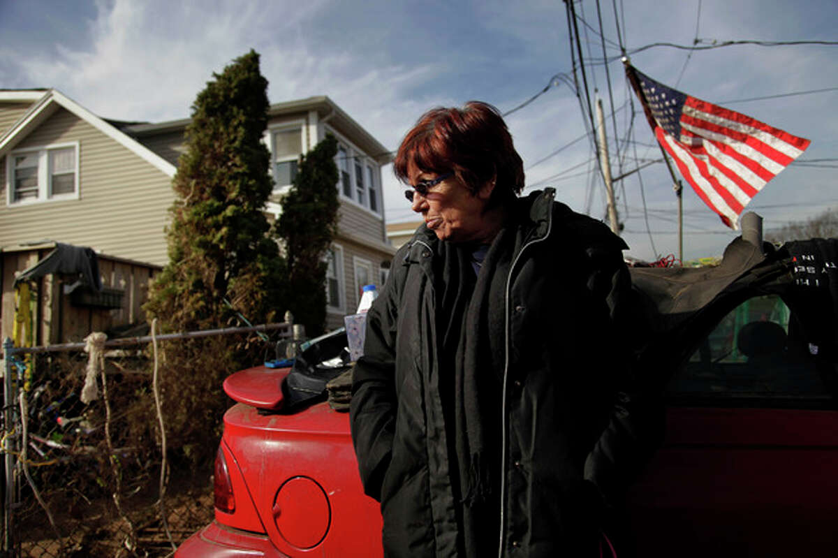 """In this Tuesday, Nov. 20, 2012 photo, Marge Gatti stands in front of her home, which was damaged by Superstorm Sandy, in the Midland Beach section of the Staten Island borough of New York. Of all things material, Gatti has nothing. And yet, on Thanksgiving Day, she will be counting her blessings this year. ?""""My sons are alive. They were trapped here,?"""" says Gatti, 67, who lived in this beige-colored home down the block from the Atlantic Ocean for 32 years. (AP Photo/Seth Wenig)"""