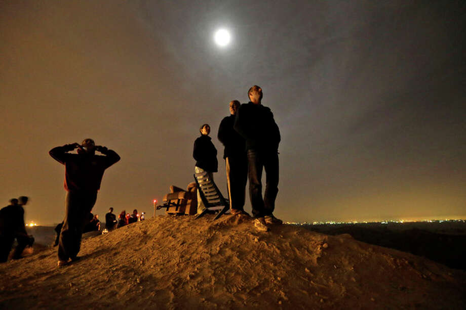 The moon illuminates Israelis standing on a hill at the Israeli town of Sderot, overlooking the Gaza Strip, background right, as they watch a missile, not seen, fired by Palestinian militants from inside Gaza towards southern Israel, Wednesday, Nov. 21, 2012, shortly before a cease-fire is announced between Israel and Hamas. Israel and the Hamas militant group agreed to a cease-fire Wednesday to end eight days of the fiercest fighting in nearly four years, promising to halt attacks on each other and ease an Israeli blockade constricting the Gaza Strip.The deal was brokered by the new Islamist government of Egypt, solidifying its role as a leader in the quickly shifting Middle East after two days of intense shuttle diplomacy that saw U.S. Secretary of State Hillary Rodham Clinton race to the region. (AP Photo/Lefteris Pitarakis) / AP