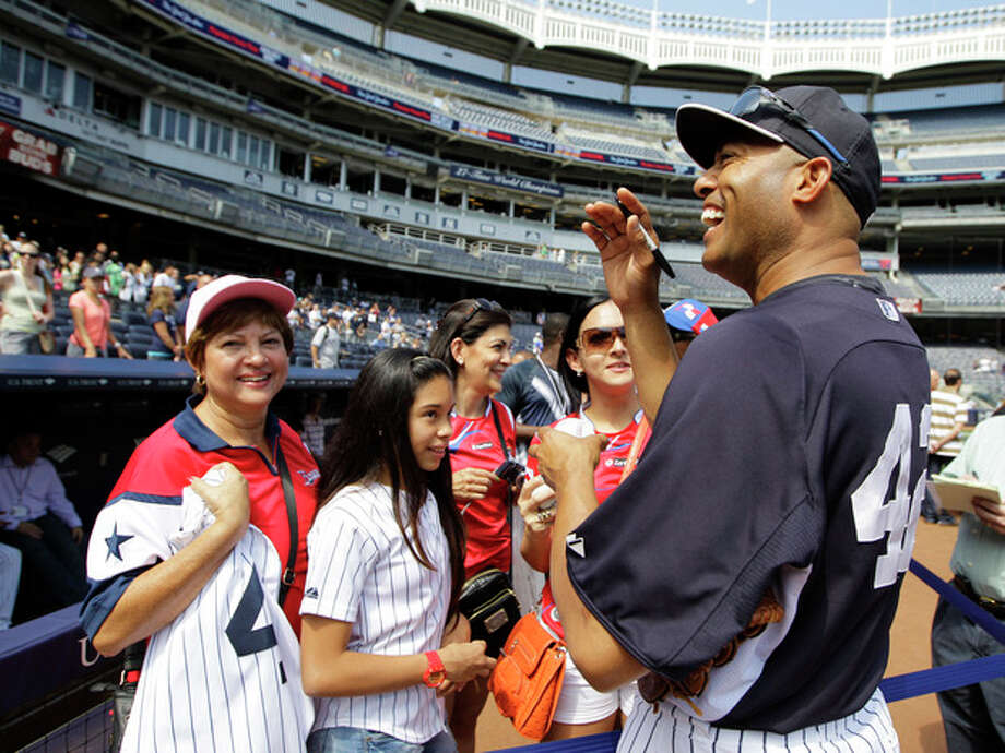 New York Yankees relief pitcher Mariano Rivera (42) waves to a group of Panamanians in the crowd as he greets others on the field before a baseball game Sunday, Aug. 11, 2013, in New York. Rivera is (AP Photo/Kathy Willens) / AP