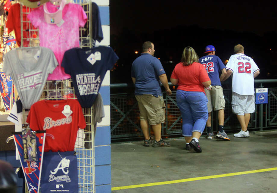 Baseball fans look over a railing at Turner Field near the scene where a man fell 60 feet from the upper deck Monday Aug. 12, 2013. Atlanta police spokesman John Chafee confirmed the death of the man, whose name has not been released. The man fell during Monday night's game between the Atlanta Braves and Philadelphia Phillies. (AP Photo/Atlanta Journal Constitution, Curtis Compton) MARIETTA DAILY OUT, GWINNETT DAILY POST OUT) LOCAL TV OUT (WXIA, WGCL, FOX 5). / Atlanta Journal Constitution