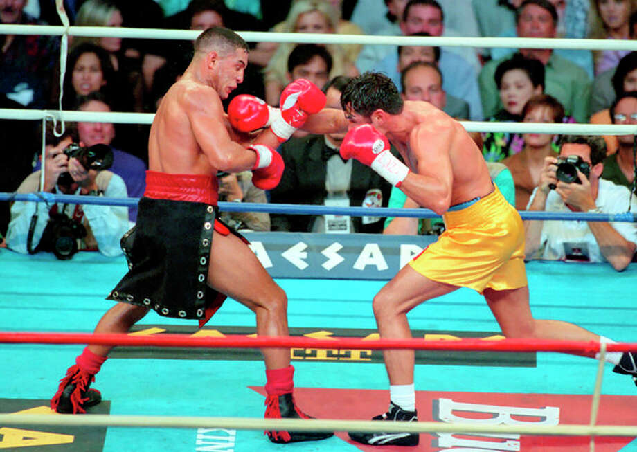 In this Sept. 13, 1997, photo provided by Las Vegas News Bureau, Hector Camacho, left, fights Oscar De La Hoya in a boxing match at Thomas and Mack Center in Las Vegas. Camacho's family tried to decide Wednesday, Nov. 21, 2012, whether he should be removed from life support after a shooting in his Puerto Rican hometown left the former boxing champion clinging to life and his fans mourning the loss of a dynamic and often troubled athlete. (AP Photo/Las Vegas News Bureau, Darrin Bush) / Las Vegas News Bureau