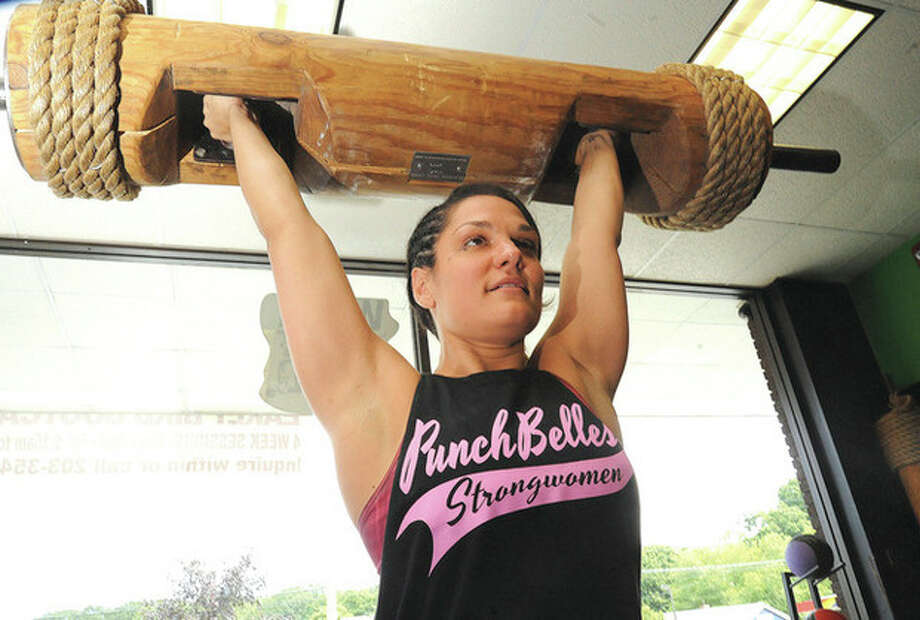 Norwalk's Punch Kettbell owner Stefanie Tropea with a 100 lb log. Stefanie will compete in the America's Strongest woman competition October 18-19 in Denison Texas. Hour photo/Matthew Vinci
