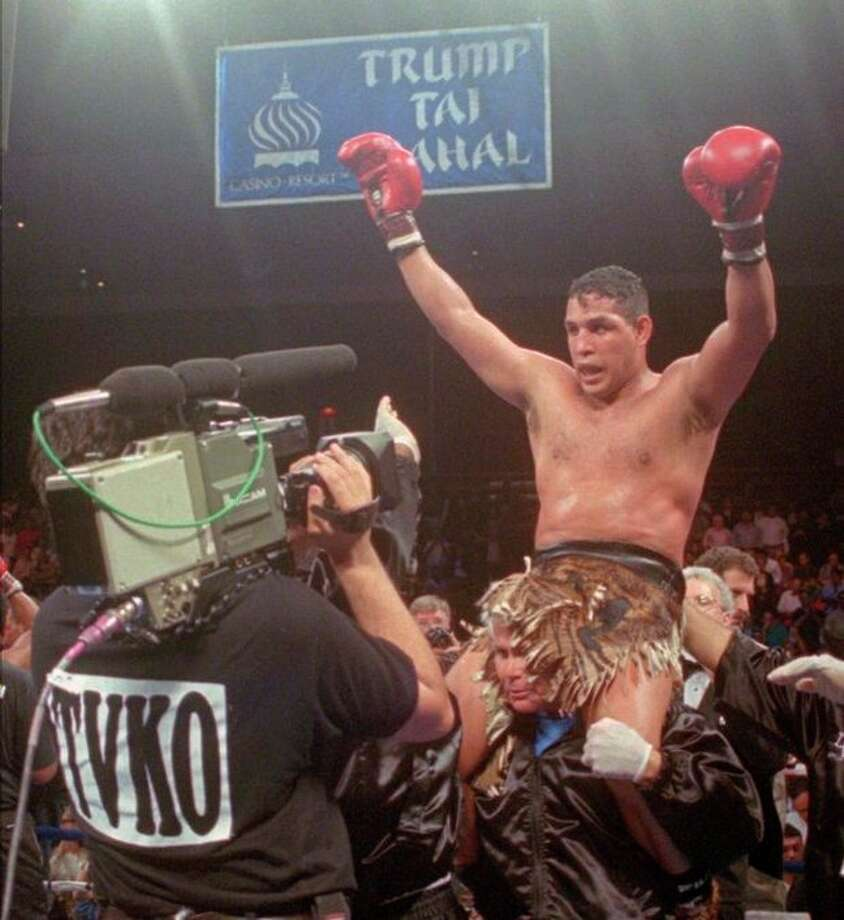 """FILE - This June 22, 1996, file photo shows Hector """"Macho"""" Camacho being lifted into the air after his unanimous decision over Roberto Duran in an IBC middleweight title fight at the Trump Taj Mahal Casino Resort in Atlantic City, N.J. Police in the Puerto Rican city of Bayamon say they found drugs inside the car in which former champion boxer Camacho was shot and critically wounded. Camacho was in critical condition Wednesday, Nov. 21, 2012, at the Centro Medico trauma center in San Juan. (AP Photo/Donna Connor, File) / AP"""