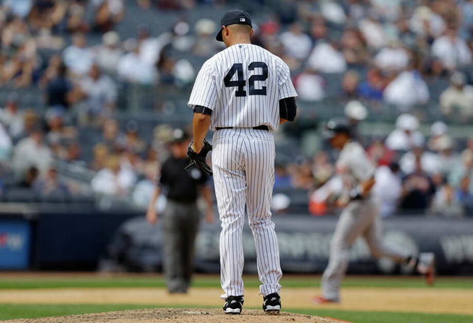 New York Yankees relief pitcher Mariano Rivera (42) reacts on the mound after allowing consecutive home runs to Detroit Tigers' Miguel Cabrera and designated hitter Victor Martinez, background right, in a baseball game on Sunday, Aug. 11, 2013, in New York. The Yankees won 5-4. (AP Photo/Kathy Willens) / AP